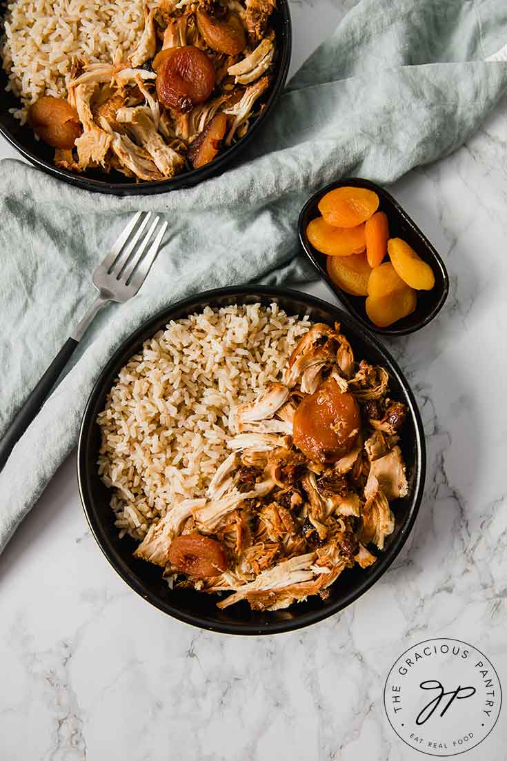 An overhead view of this Clean Eating Curry Chicken dish shows tow bowls filled with the curry chicken and brown rice. A small bowl of dried apricots sits to the side of these bowl on the right, with a fork on the left.