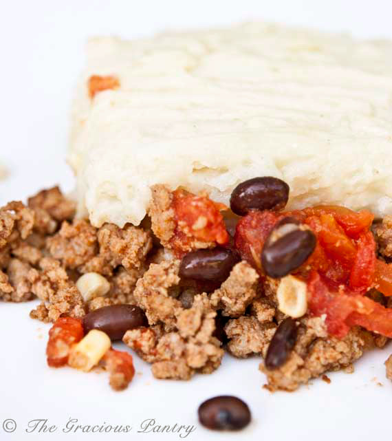 A servings of this Clean Eating Mexican Shepherds Pie sits on a rounds white plate on a white background. You can see the layers of the casserole with the white potato layer on top and the ground meat with beans on the bottoms.