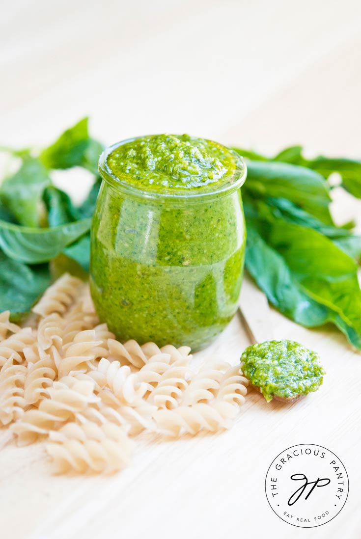 A small, clear jar of this Clean Eating Traditional Pesto Sauce sits on a light wood surface surrounded by dry, spiral pasta noodles and fresh basil leaves.