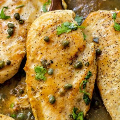 And up close view of this lemon caper chicken still sitting in the skillet with a serving spoon lifting up one of the chicken breasts. It has capers sprinkled over it as well as fresh parsley.