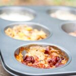 A muffin tin filled with different flavored oats sits ready to serve. Find out how to make this Muffin Tin Oatmeal Recipe below!