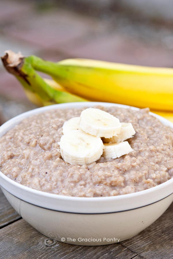 A bowl of this Clean Eating Banana Bread Oatmeal sits on a wooden table top with two unpeeled bananas next to it. The oatmeal has a few slices of fresh banana on top.