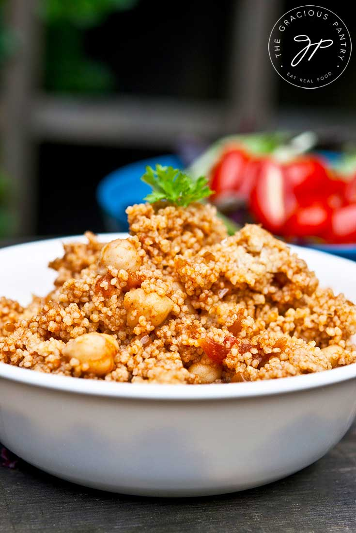 A bowl sits on a wooden table filled with this Indian CousCous Recipe. Fresh tomatoes sit in the background.