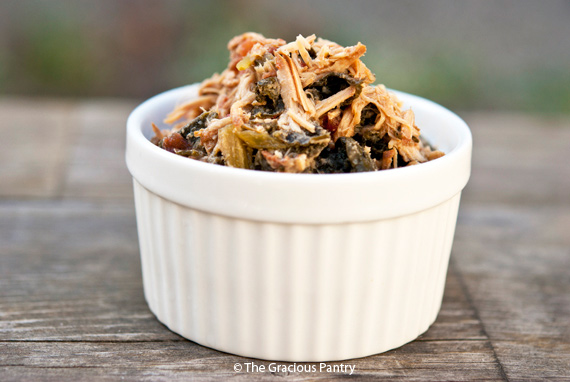 Clean Eating Slow Cooker Pork & Kale shown in a white bowl. The pork is shredded and you can see bits of the kale.