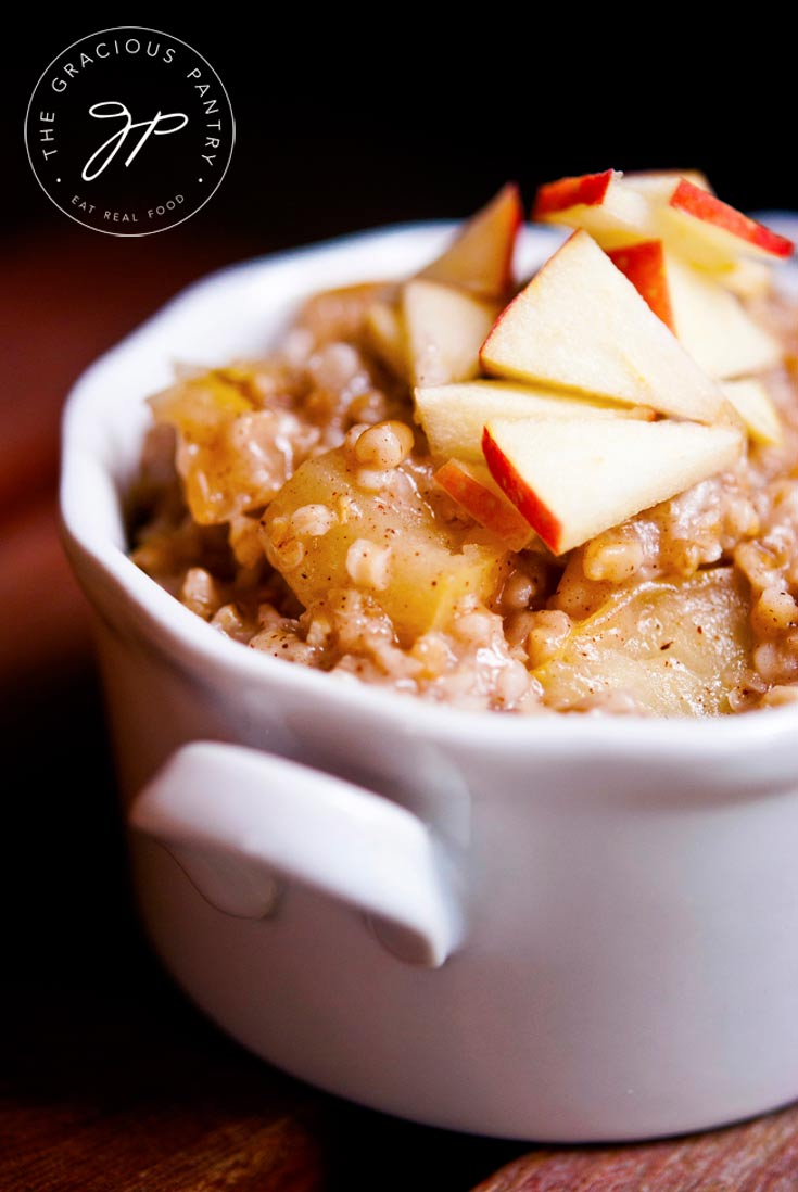 A closeup shot of this Clean Eating Apple Pie Oatmeal in a white bowl with fresh cut apples on top for garnish.