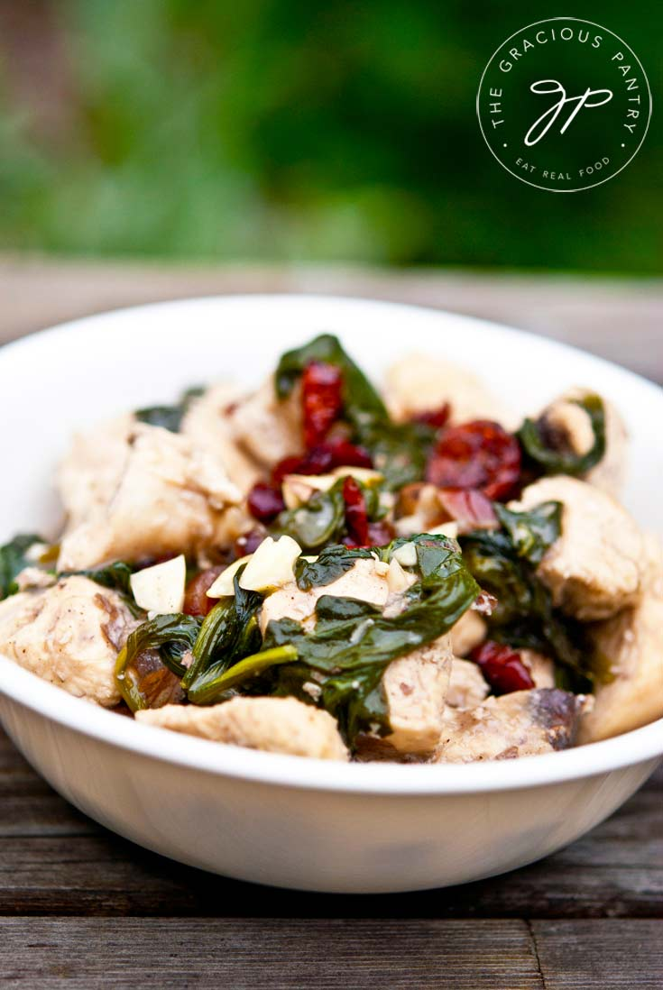 Clean Eating Coconut Almond Cranberry Chicken in a white bowl, shown up close. You see the chances of chicken, the red cranberries and plenty of spinach.