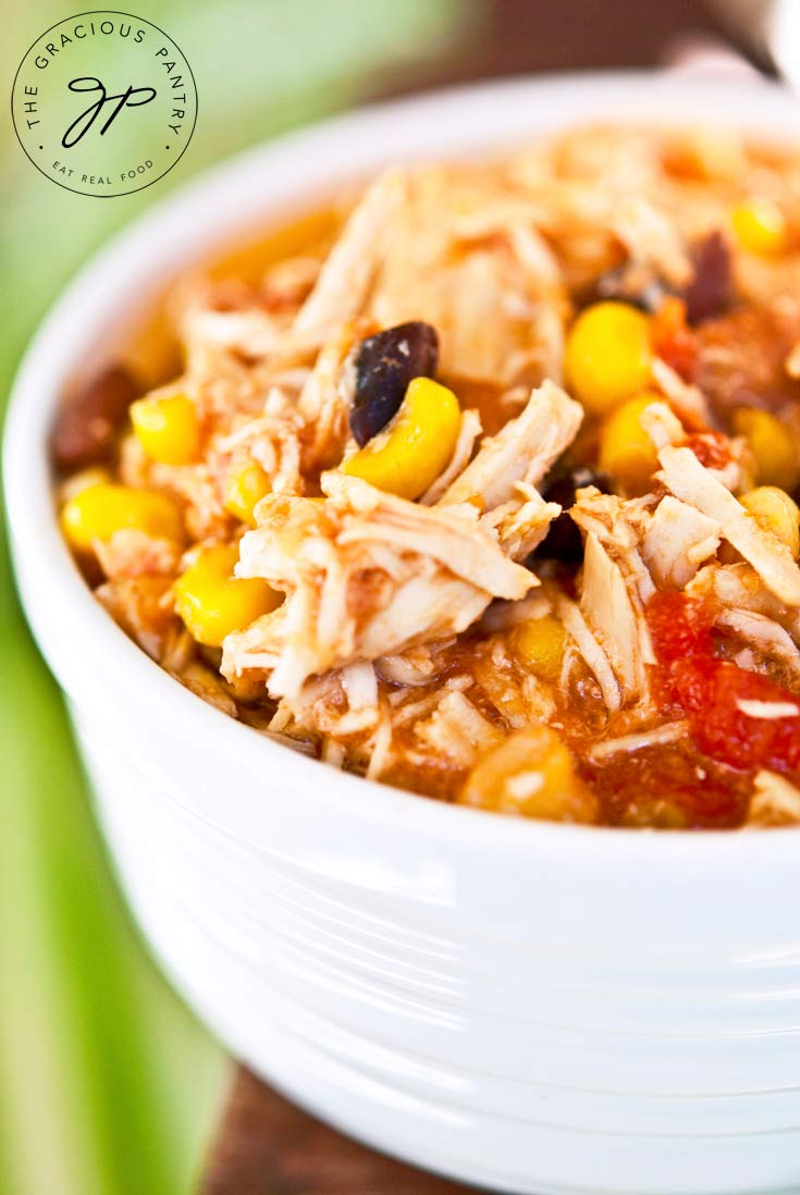A closeup shot of this Clean Eating Slow Cooker Southwestern 2 Bean Chicken shows the shredded chicken and beans in a white bowl with a brown background.
