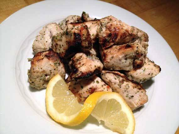 Clean eating grilled chicken souvlaki recipe served on a white plate with a twisted lemon slice.
