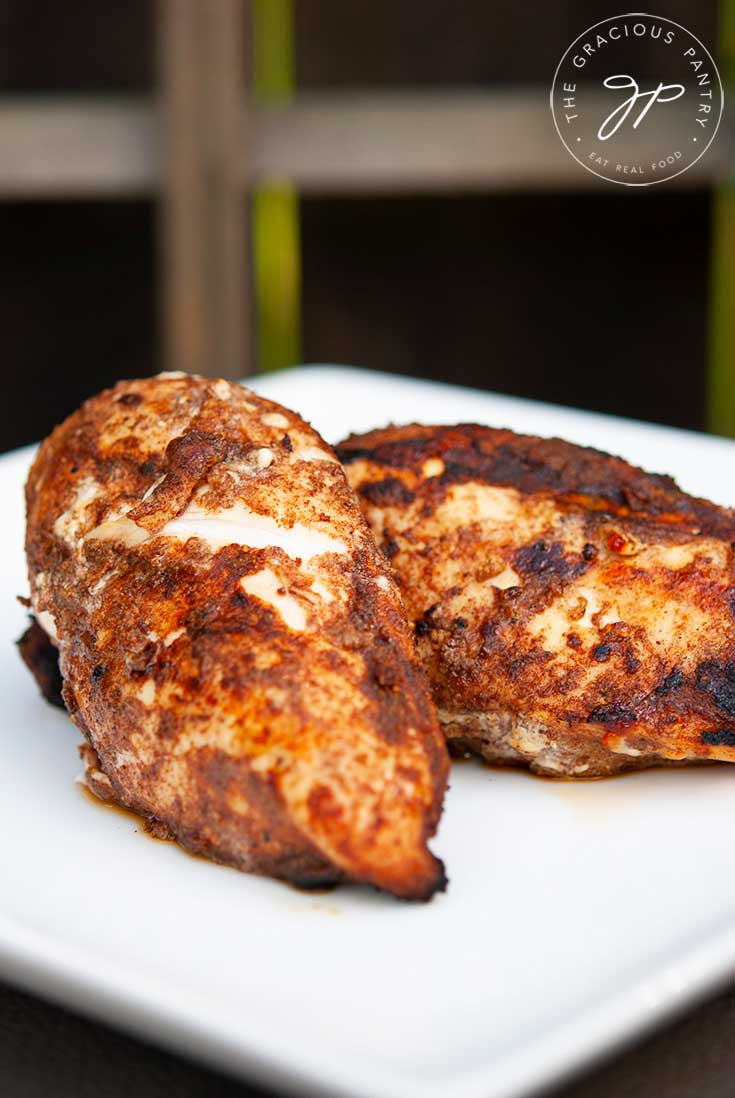 Two pieces of golden-brown, grilled chicken sit seasoned, just of the grill, with this Middle Eastern Grilled Chicken Rub.