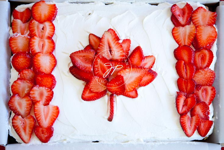 A view of this Clean Eating Canada Day Cake from overhead, looking down. The Canadian flag design is made from sliced, red strawberries placed over white cake frosting.