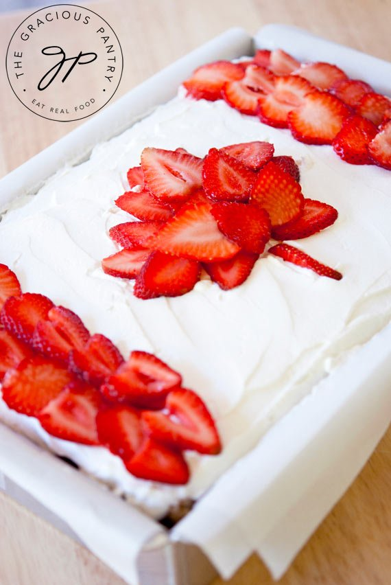 A view of this Clean Eating Canada Day Cake from the side. You can see the white frosting over the top and the bright red strawberry slices placed in the form of the Canadian flag.