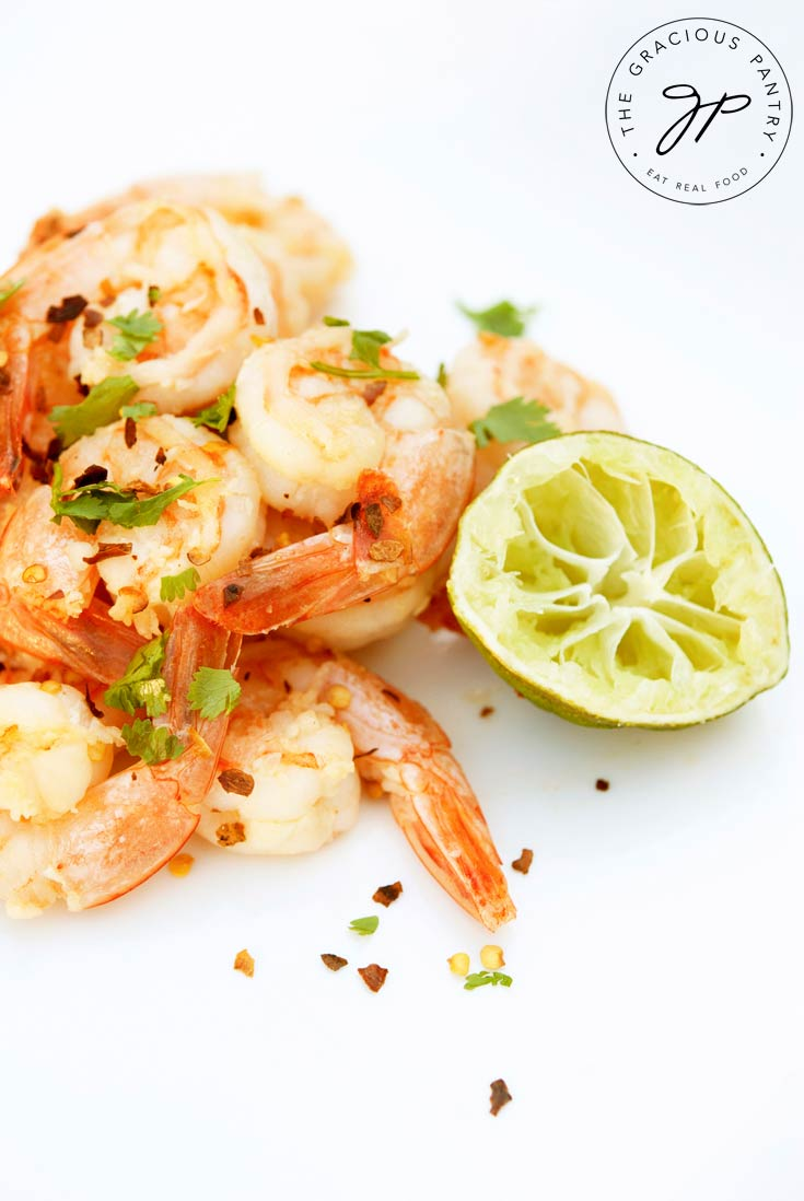 Clean Eating Garlic Lime Shrimp on a white background with a few red pepper flakes sprinkled over them. A half lime that has been squeezed sits next to the shrimp.