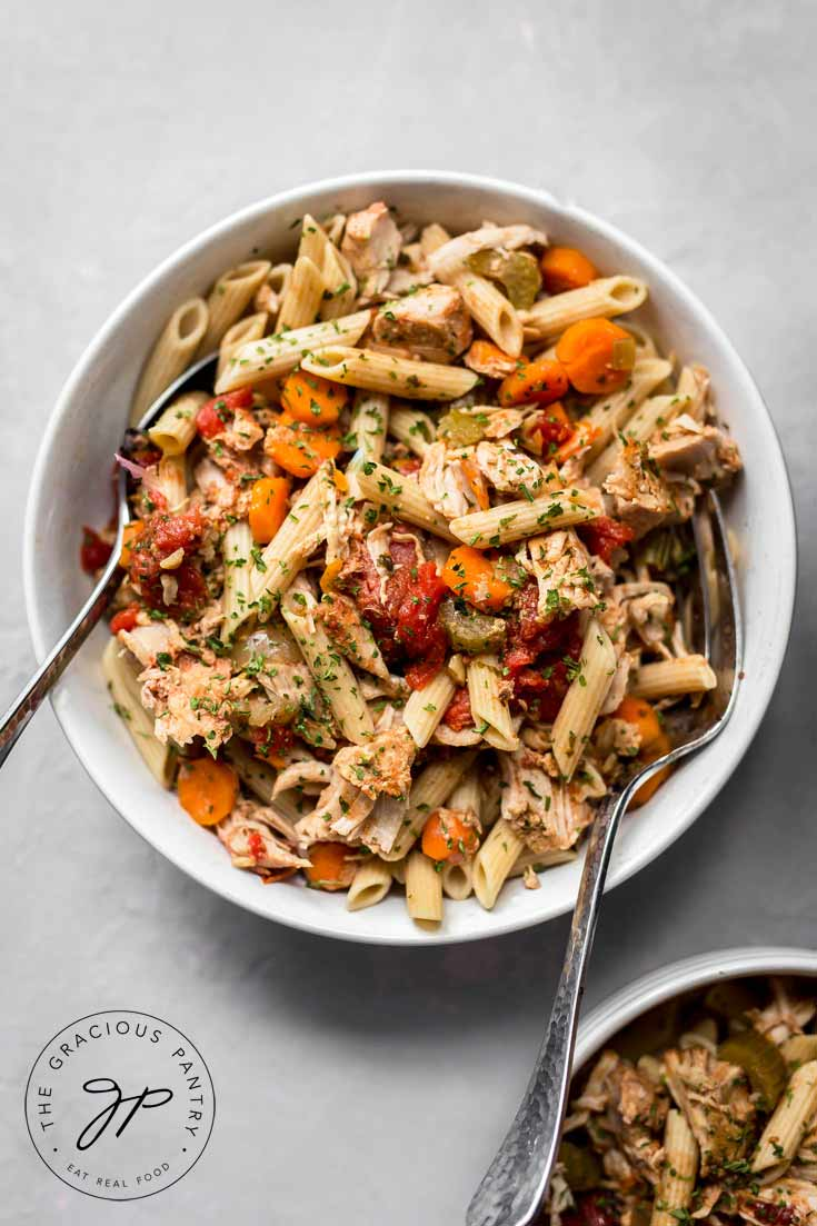 A close up view of a single while bowl containing this Clean Eating Slow Cooker Pork Ragout. It has two spoons on either side of the bowl, ready to serve this bowl of deliciousness.