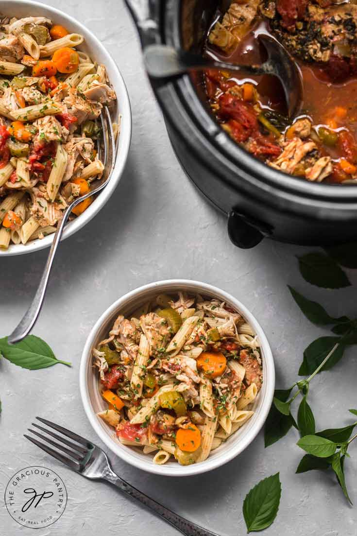 This Clean Eating Slow Cooker Pork Ragout has just been served. The bowls of food are still sitting next to the slow cooker and both white dishes are full and ready to serve.