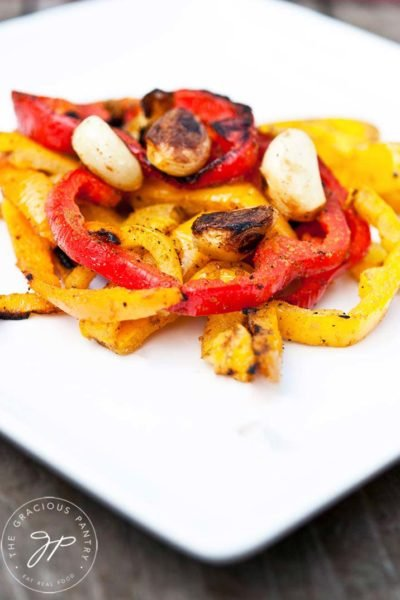 A white plate holds some red and yellow bell peppers with garlic cloves sitting on top from this Clean Eating Barbecued Bell Pepper Recipe.