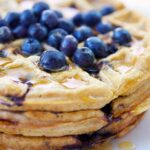 Blueberry waffles stacked on top of each other with fresh blueberries sprinkled over the top.