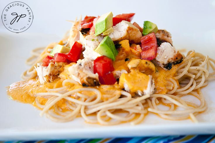 A side view of this Chicken Alfredo Pasta shows the pasta, sauce, chicken and toppings such as tomatoes and avocado.