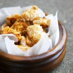 A wooden bowl with a parchment liner sits filled with golden brown popcorn shrimp.