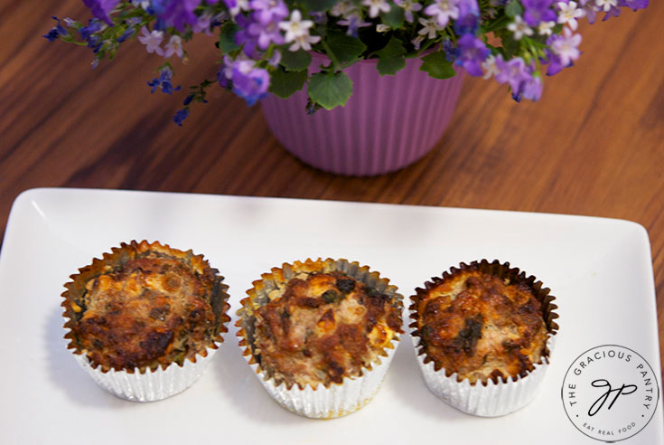 A platter of these Spinach And Feta Breakfast Muffins sits next to a potted plant on the table.