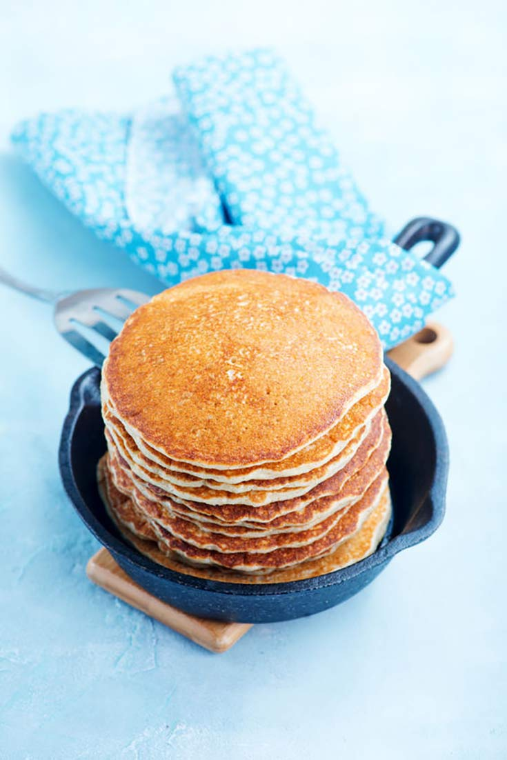 A stack of baked pancakes sits in a skillet on a table with a blue tablecloth and napkin. A fork rests on the side of the pan.