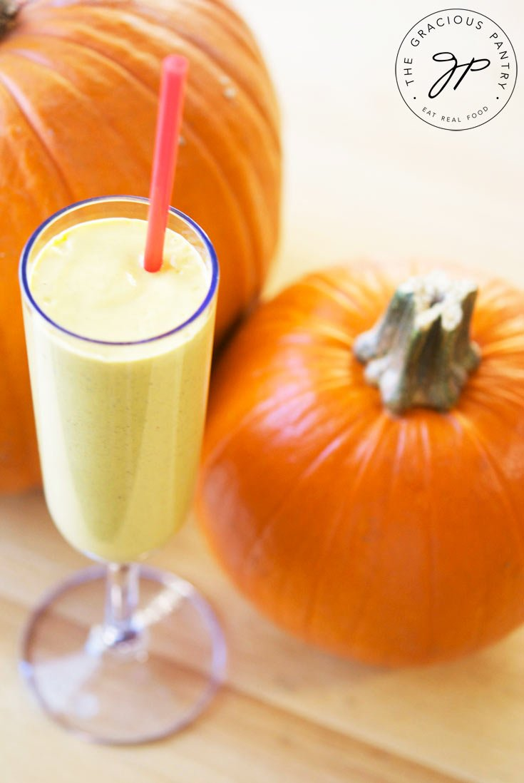A single champagne glass filled with this Clean Eating Pumpkin Pie Oatmeal Smoothie sits between two pumpkins.