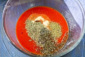 Combining the tomato sauce and spices in a mixing bowl.