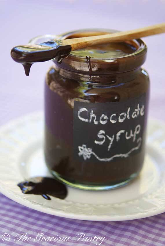 A clear jar with a chalkboard label sits on a plate without a lid. It has a small wooden spoon with the tip covered in chocolate, laying across the top of the jar filled with this Clean Eating Chocolate Syrup