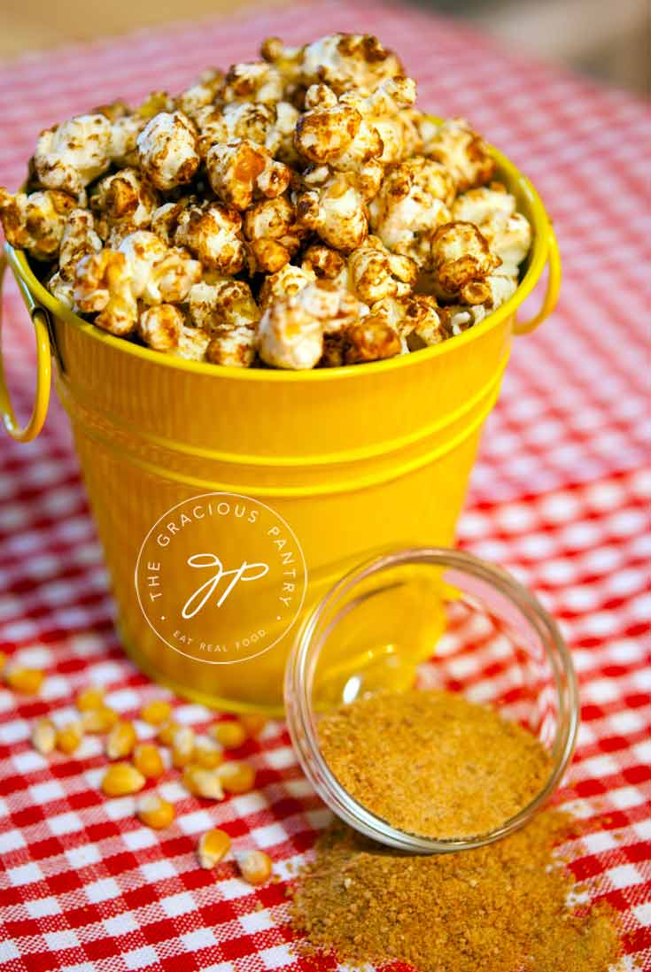 Clean Eating Kettle Corn in a small, yellow, metal bucket sitting on a red and white checkered tablecloth