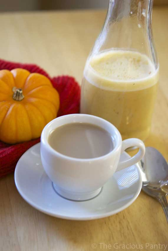 A bottle of Clean Eating Pumpkin Pie Coffee Creamer next to a small mug of coffee and mini pumpkin arranged on a table.