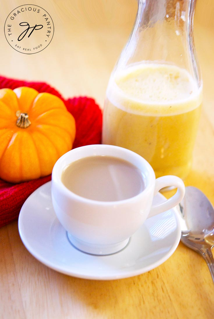 A cup of coffee sits, flavored with this Pumpkin Spice Coffee Creamer, waiting to be enjoyed.