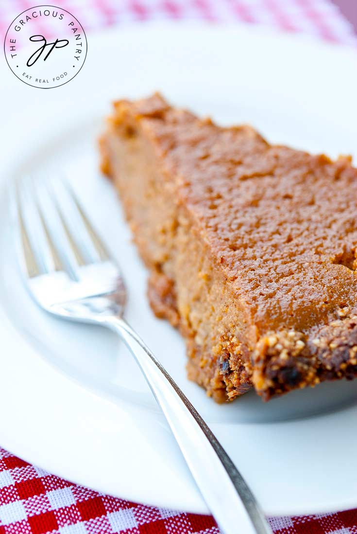 A slice of this Sweet Potato Pie Recipe sits on a white plate with a fork next to it, ready to enjoy.