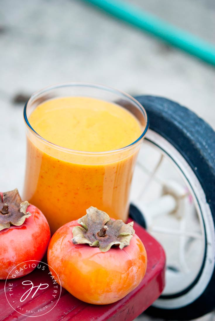 A glass of Clean Eating Kid's Persimmon Smoothie sits on the back step of a red tricycle with two persimmons sitting in front of the glass.
