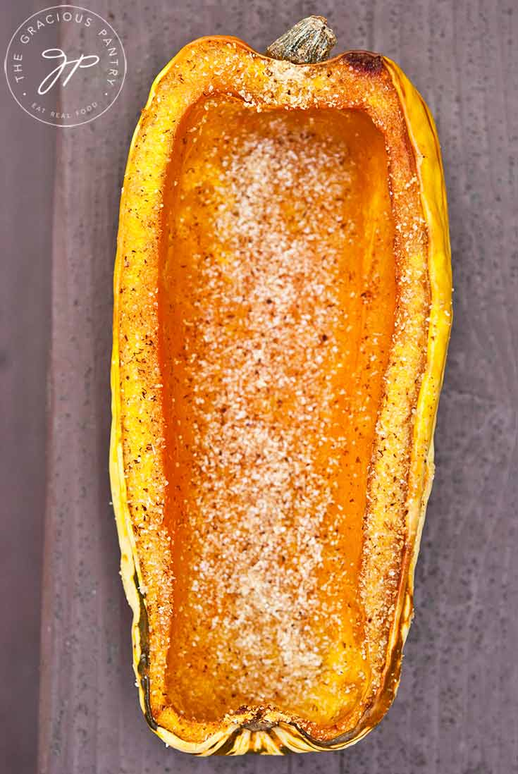 Half a baked delicata squash sits on a wooden plank, slightly golden brown from the oven and ready to eat.