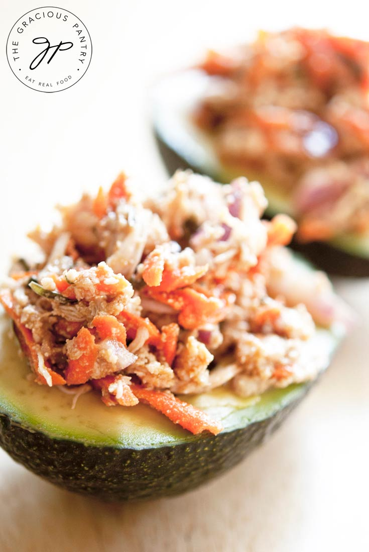 This Clean Eating Chicken Avocado Salad is shown up close with the chicken salad served on top of a half of an avocado.