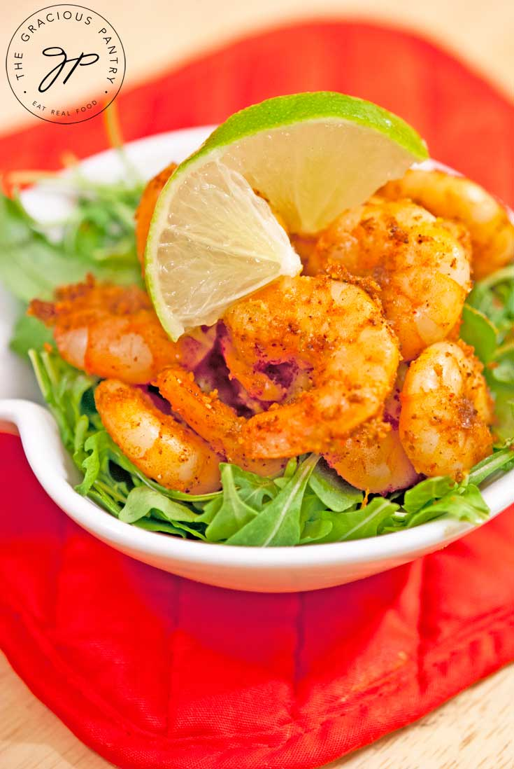 Clean Eating Taco Shrimp piled high in a white bowl on a bed of leafy greens and a twisted slice of lime placed on top for garnish.