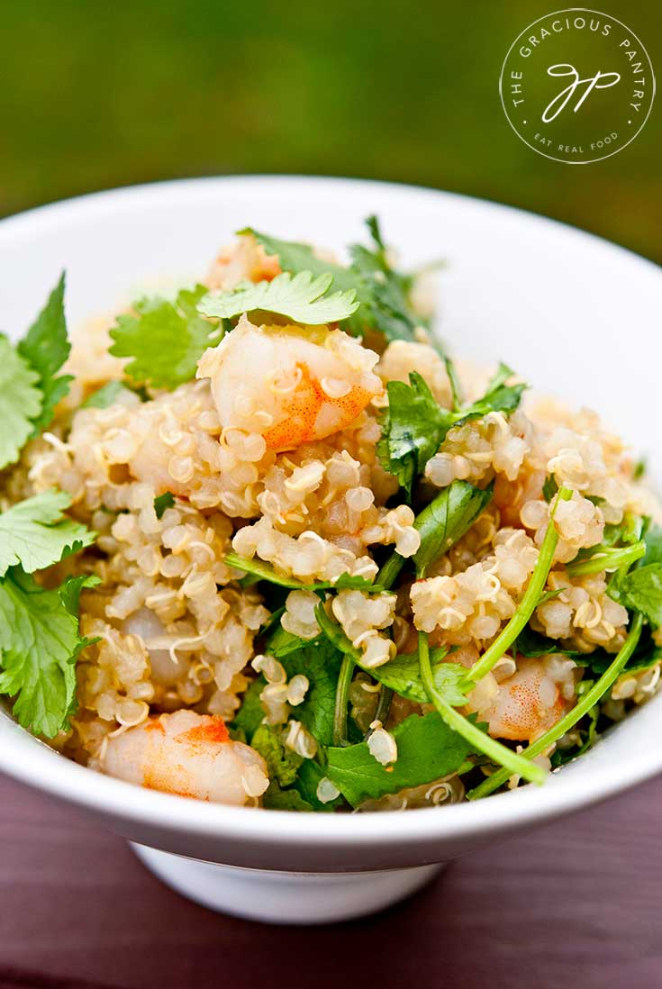 A white bowl sits on a wood table filled with a single servings of this Clean Eating Quinoa Garlic Shrimp & Cilantro Salad Recipe. The shrimp and cilantro are freshly mixed into the grains of quinoa.