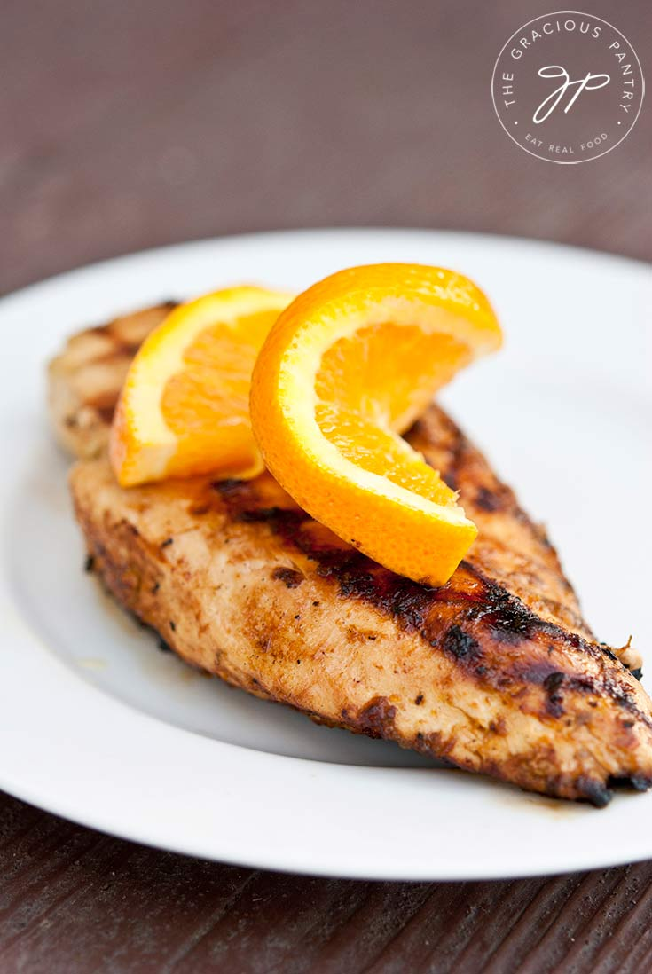 Clean Eating Citrus Grilled Chicken breast served on white plate with a slice of orange twisted and placed on top for garnish.