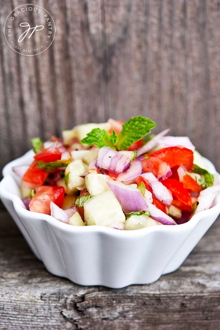 A white bowl sits on a wooden ledge, filled with this colorful Shirazi Salad.