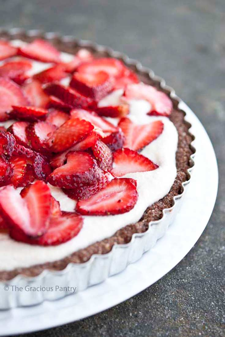 A side view of this clean eating grain free cashew strawberry tart shows the brown, nut-based crust, the white cashew cream filling and sliced, fresh strawberries garnishing the top of the tart.