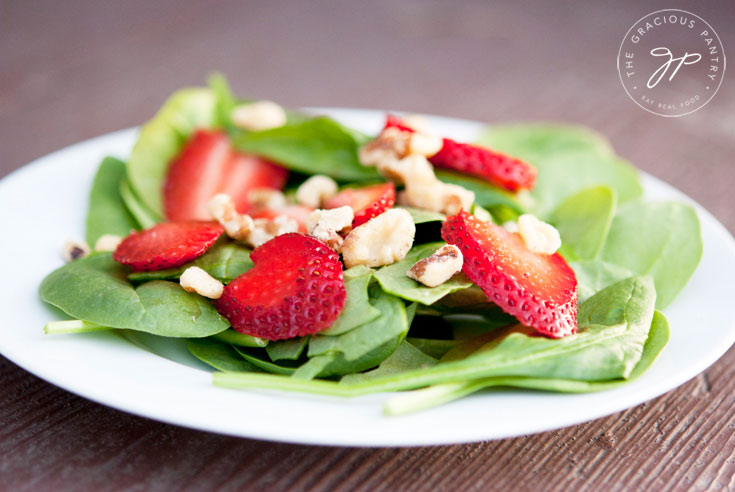 Clean Eating Strawberry Spinach Salad served and ready to eat off a small, white plate.