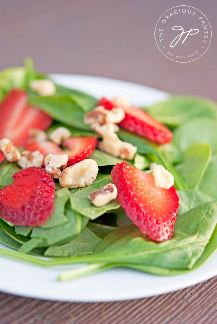 Clean Eating Strawberry Spinach Salad served on a white plate and shown up close. You can easily see the spinach, walnut pieces and strawberry slices. The avocado is not shown in the photo.