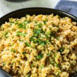 A bowl or delicious, brown rice pilaf sits in a black bowl, ready to serve and enjoy.
