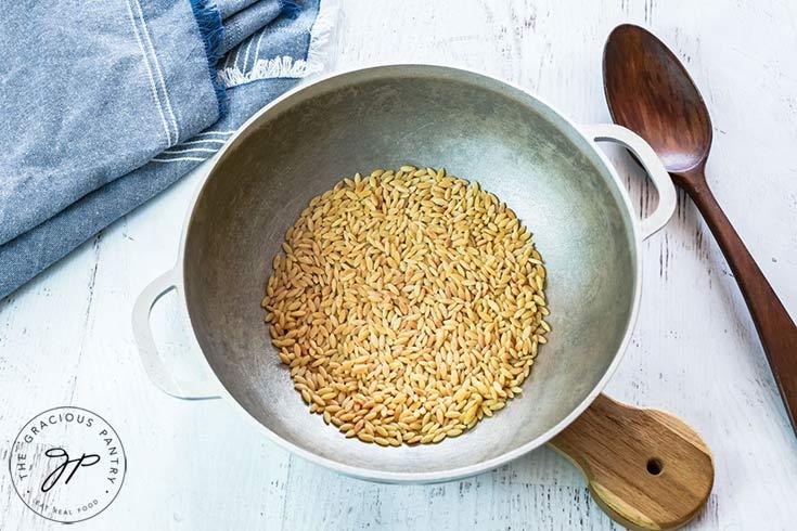 Roasting the whole grain orzo.