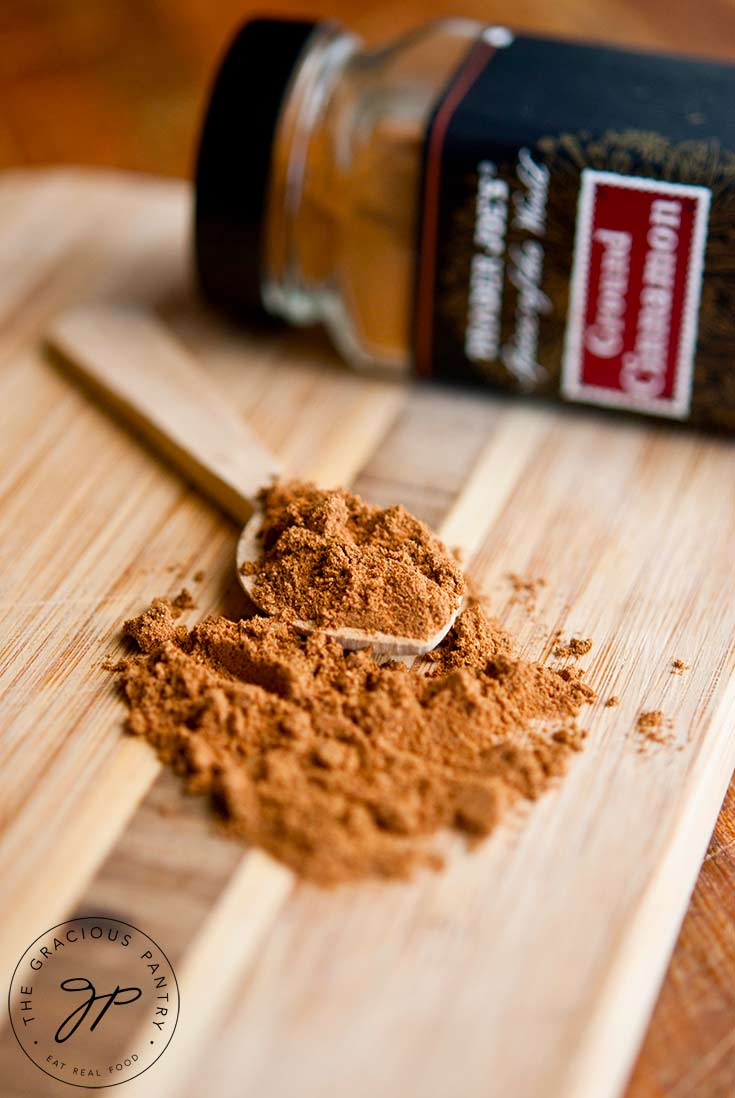 Some of this Pumpkin Pie Spice Recipe lays on a cutting board with a small wooden spoon ready to scoop some up. A bottle of cinnamon lays on it's side in the background.