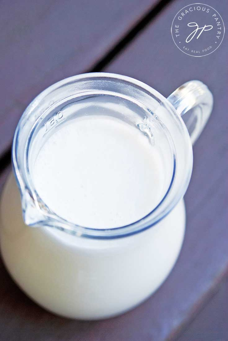 A pitcher of fresh almond milk sits on a table, ready to pour in this guide, how to make almond milk.