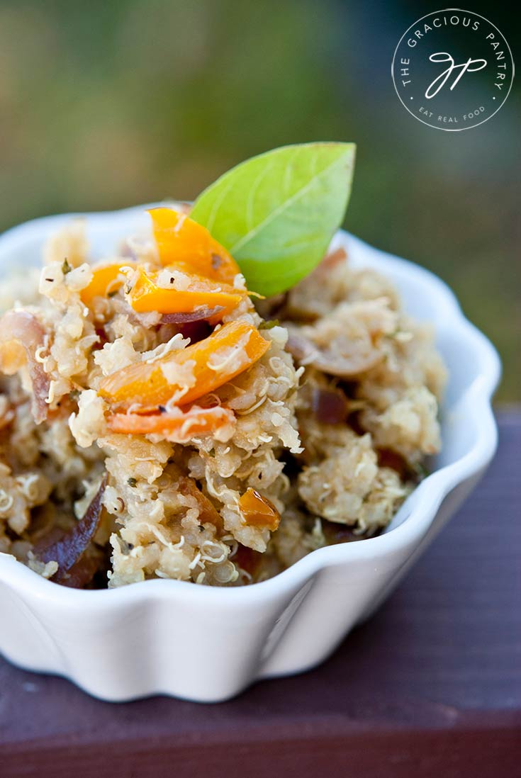 A white bowl sits filled with this Vegetable Quinoa Recipe and is garnished with a green leaf.