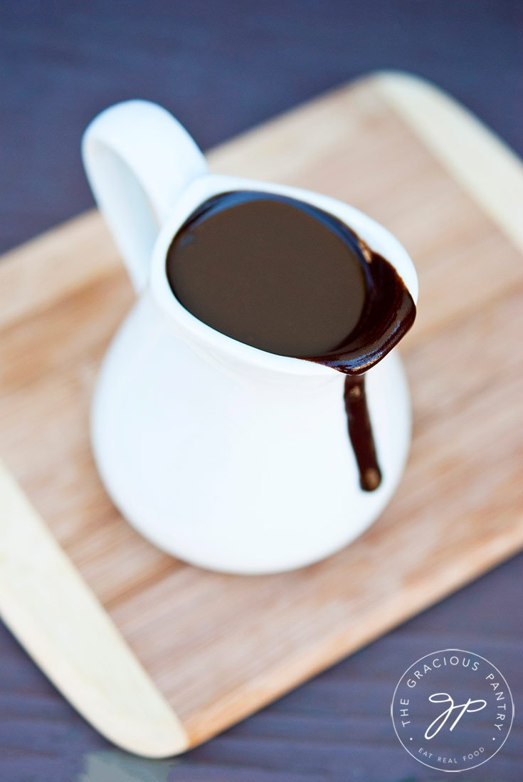 A white pitcher filled with this Clean Eating Coconut Fudge Sauce sits on a small cutting board as a bit of the fudge sauce runs down the front of the pitcher.