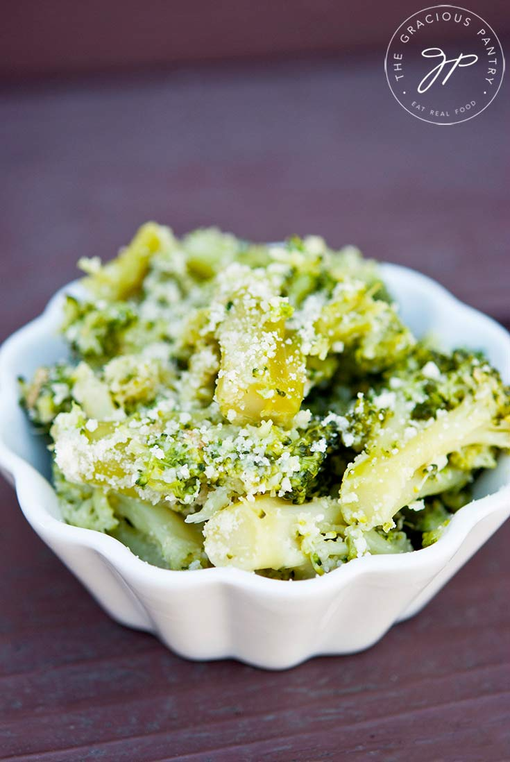 A white bowl sits filled with this Garlic Broccoli Recipe. You can see the specs of white parmesan coating the bright green broccoli florets.