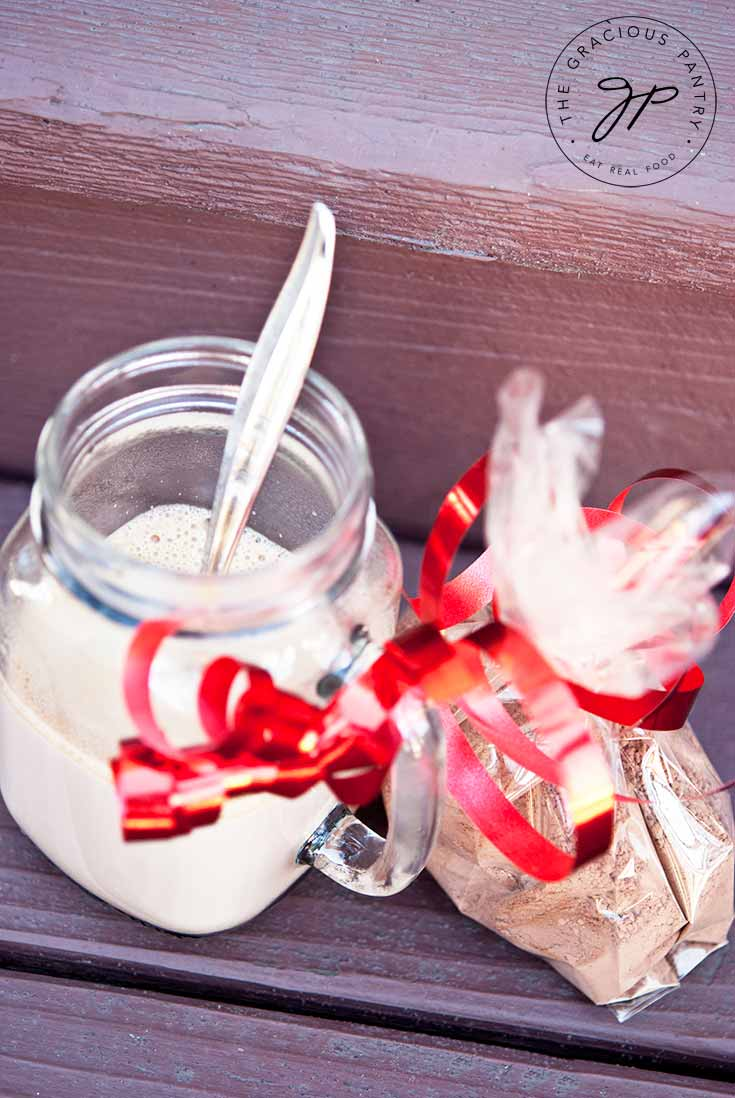 A mason jar mug sits on a wooden background filled with hot chocolate made from this Clean Eating Hot Chocolate Mix. A clear bag sits next to it filled with the dry mix and tied with a red ribbon.
