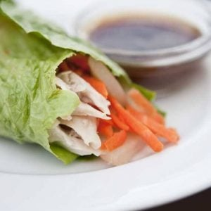 A single wrap from this Asian Lettuce Wraps recipe sits on a plate next to dipping sauce, ready to enjoy.